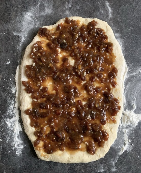 After half an hour, sprinkle the cinnamon over the dough, and then spoon the marzipan over the whole of the dough, right up to the edge. Roll the dough up from the long side, so you have a long sausage shape.