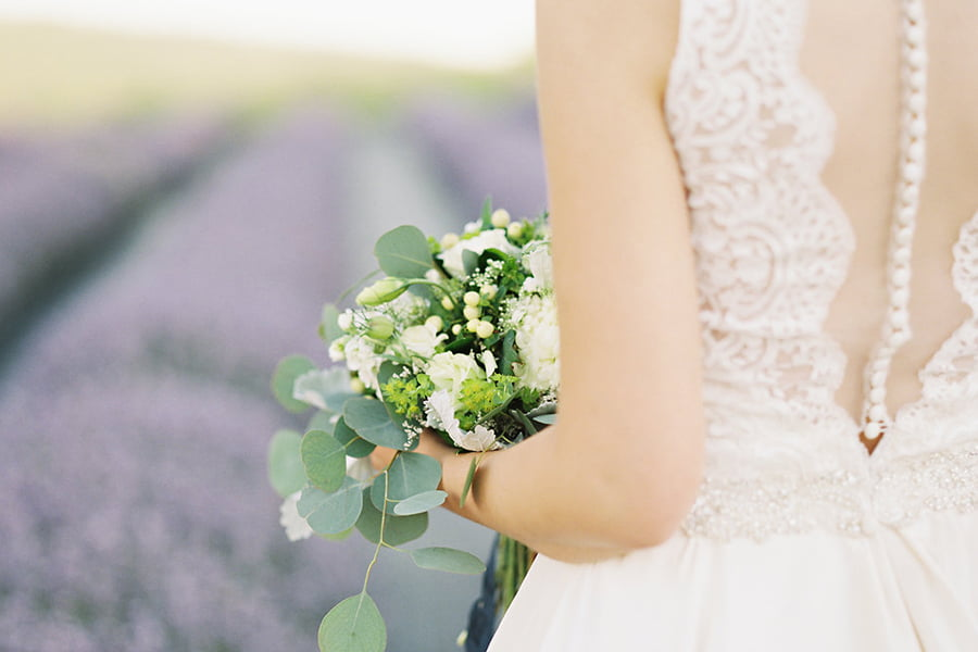 Bouquet and back of Bride's dress with lavender field backdrop.
