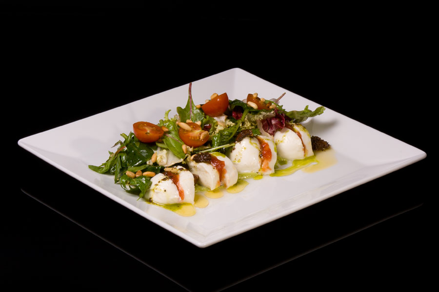 Mozzarella cheese salad with candied tomato, pine nuts, pesto and basil