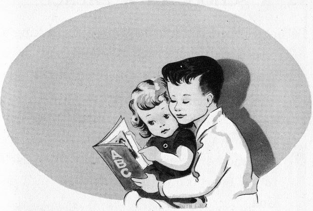 Boy helping younger sister to read a book