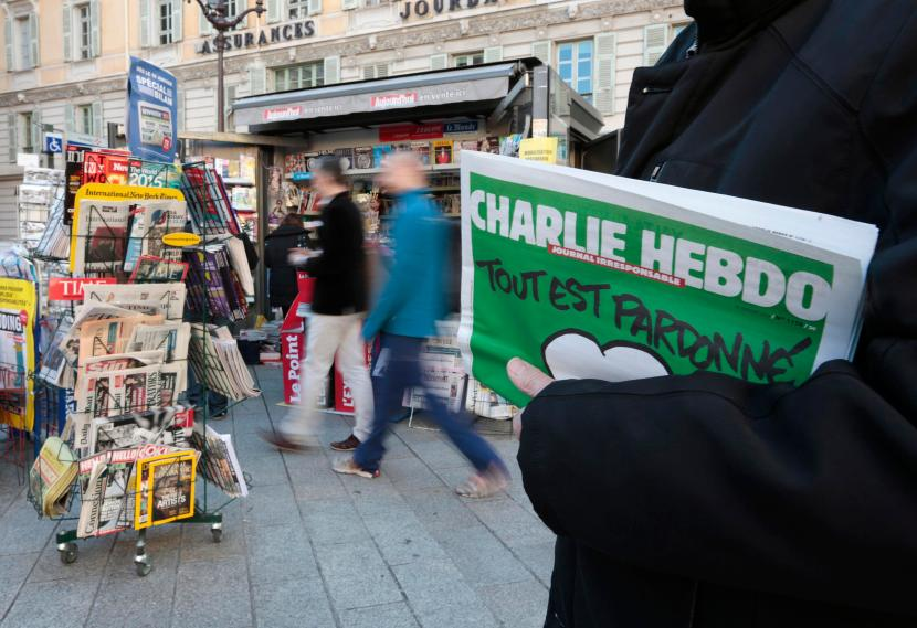 A man holds the new issue of satirical French weekly Charlie Hebdo at a kiosk in Nice
