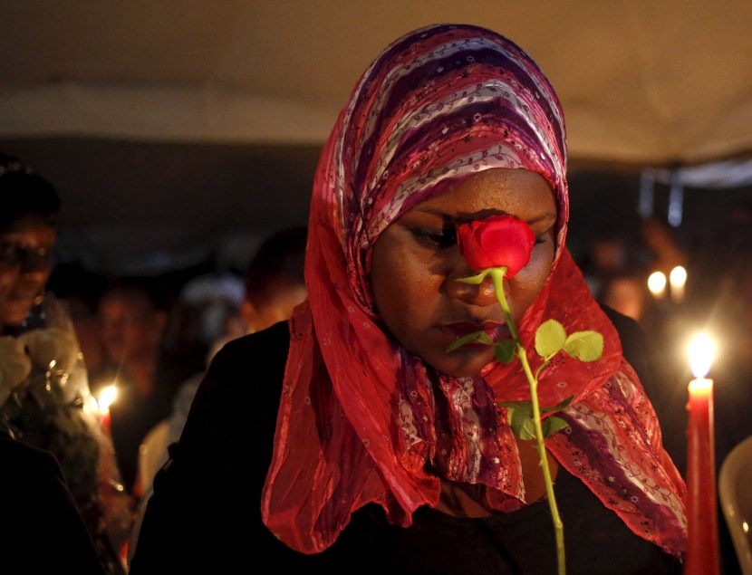 "A woman holds a rose as she prays during a memorial vigil following an attack by gunmen at the Garissa University College, at the ""Freedom Corner"" in Nairobi"