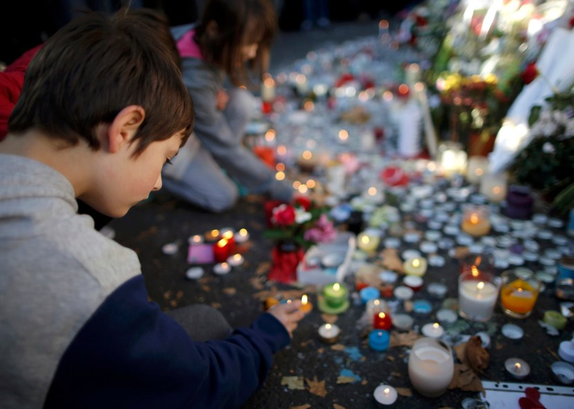 Children light candles near the site of the attack at the Bataclan concert hall in Paris, November 15, 2015.    REUTERS/Christian Hartmann