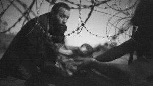 """La foto chiamata """"Speranza di una nuova vita"""" ha vinto il premio World press photo 2016 ed è stata scattata dal fotografo Warren Richardson. Un bambino molto piccolo viene passato dalle braccia di un profugo attraverso le recinzioni tra i campi di Röszke, al confine tra Serbia e Ungheria"""