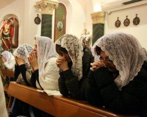 Donne che pregano con il velo, in Chiesa.