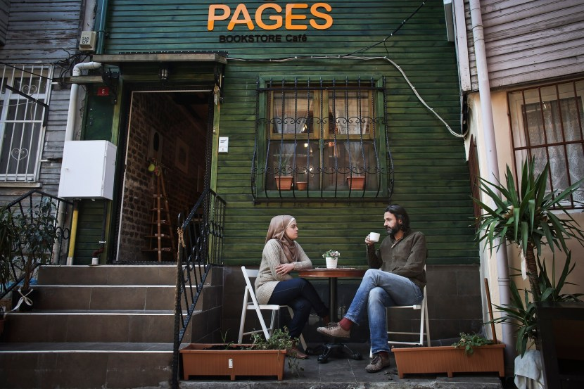 Samer Alkadri, a Syrian painter and graphic designer from Damascus poses for a photo, as he sits outside the Pages cafe and bookstore with one of his employees, in Istanbul, Sunday, Dec. 6, 2015. Over years now, Syrian refugees have become woven in to the frenetic life of this sprawling city, opening restaurants and cafes, performing as street musicians on the city's busiest boulevard, and, everywhere it seems, panhandling on street corners, holding out their Syrian passports to elicit the sympathies of passersby. At Pages, a bookstore and cafe in a three-story wooden house in a tidy cul-de-sac up a hill in this city's oldest quarter, a literary refuge has blossomed for young Arabs in exile. (Photo Credit/Tara Todras-Whitehill for the New York Times)                              NYTCREDIT: Tara Todras-Whitehill for The New York Times