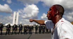 Manifestante aggredito durante le proteste contro il Governo Temer a Brasília