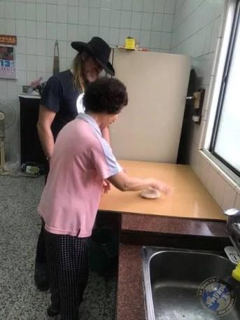 La abuela poniendo energía para amasar la masa de la pizza
