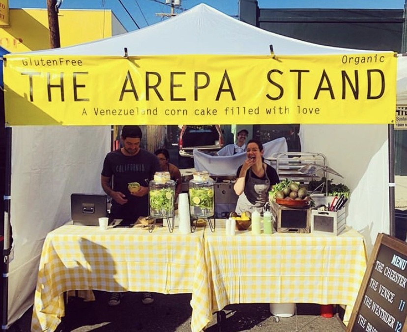Mercedes Rojas, right, takes a bite of an arepa next to her brother Zeus Ferrini.; Credit: The Arepa Stand