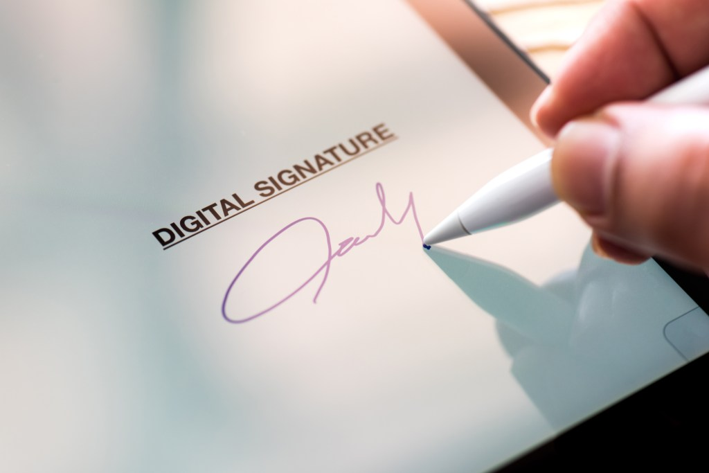 Person is using a tablet device to easily digitally sign a contract. E-sign is an essential tool for your survival toolkit.