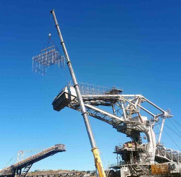 Crane handling scaffold on industrial project