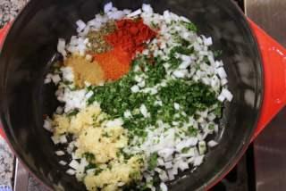 Cocinar las cebollas, el ajo, hierbas y especias en aceite hasta que la cebolla esté suave