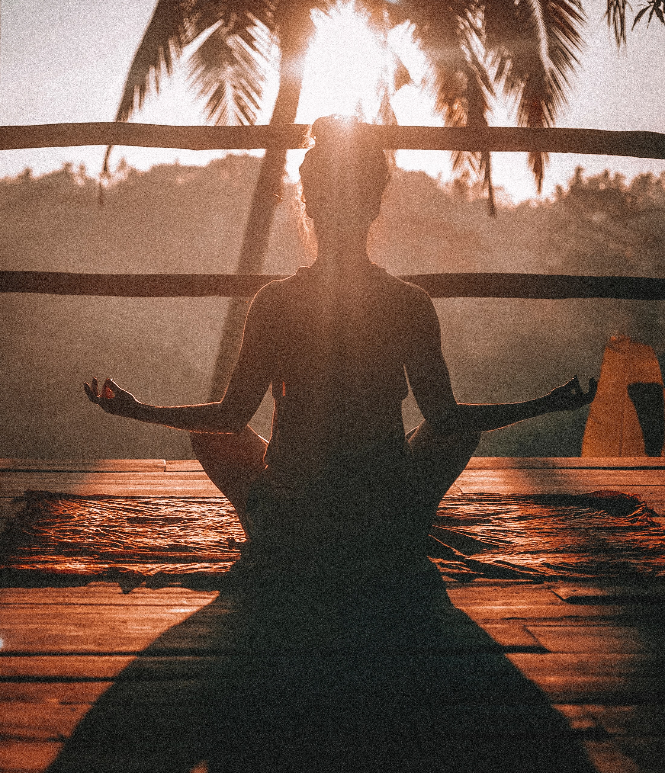 A woman meditating at sunset.