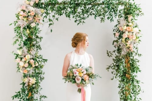 Bride standing underneath a floral arbor or greenery and blooms