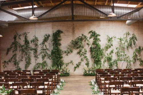 Modern Industrial Wedding Venue warmed up with ascending greenery from the floor