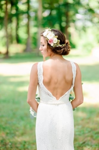 Floral comb on the left side of bride low bun up-do with ivory and blush flowers
