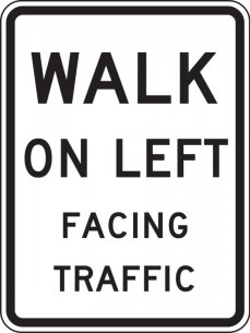 Sign directing how to walk on a street with no sidewalks