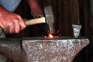 Image of blacksmith hammer striking hot iron on an anvil