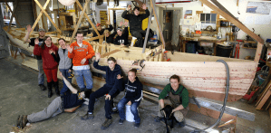 Image of boat building program students with AmeriCorp instructors and Museum staff in the shop with a partially built boat