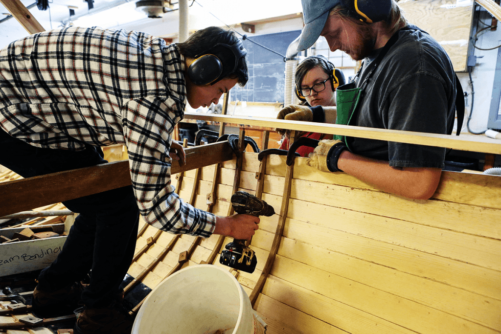 Students working on the inside of a new boat