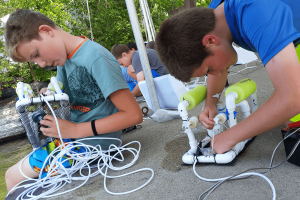 Two boys work on robots at camp