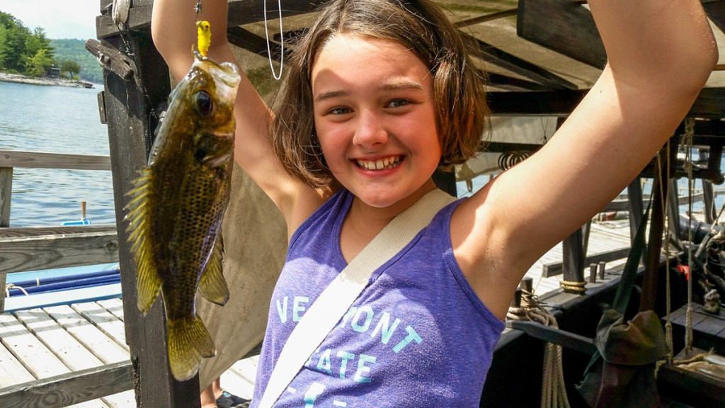 Young girl with a fish caught at camp