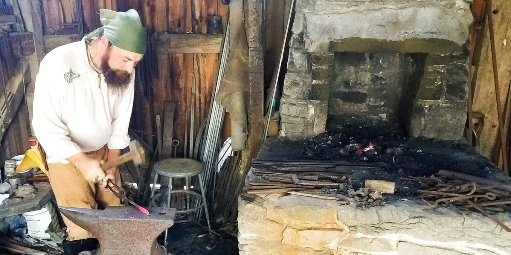 Man works at a traditional 18th century style forge