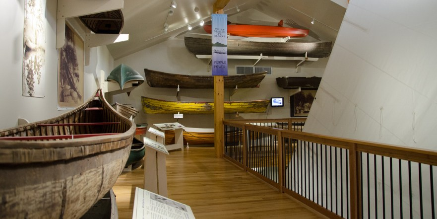 Interior view of the Museum's small watercraft center with boats on the walls