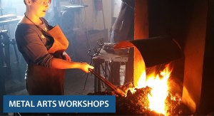Teen manages the fire of a blacksmith forge
