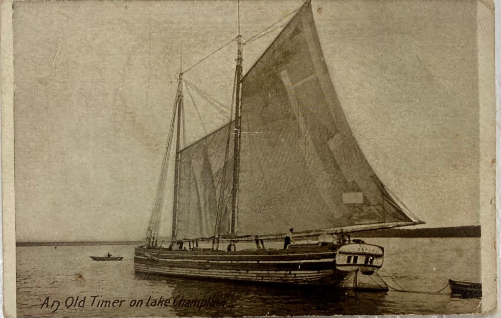 An old sepia-colored photograph of a sailing canal schooner traveling on a lake with sails open