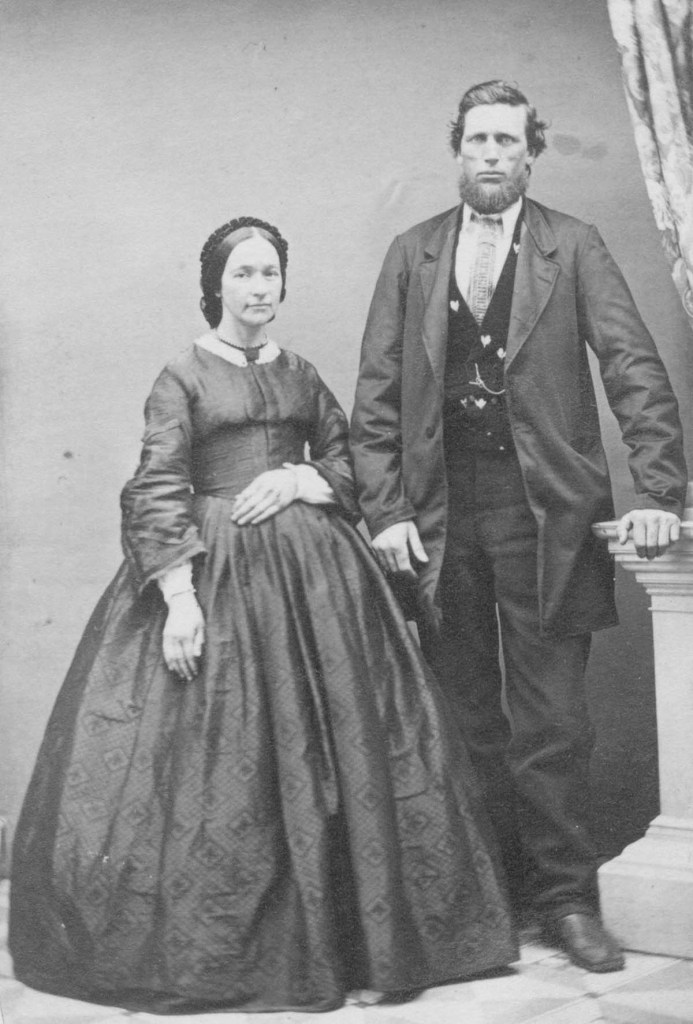 A black and white photograph showing a woman standing on the left and a man standing next to her on the right. They are in formal nineteenth century clothes and look at the camera with neutral expressions.