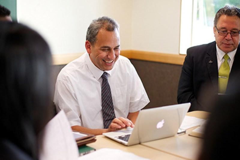 Un hombre sonríe mientras usa una computadora portátil