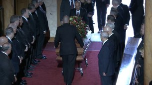 The packed Tabernacle stands as Elder Scott's casket is brought inside.