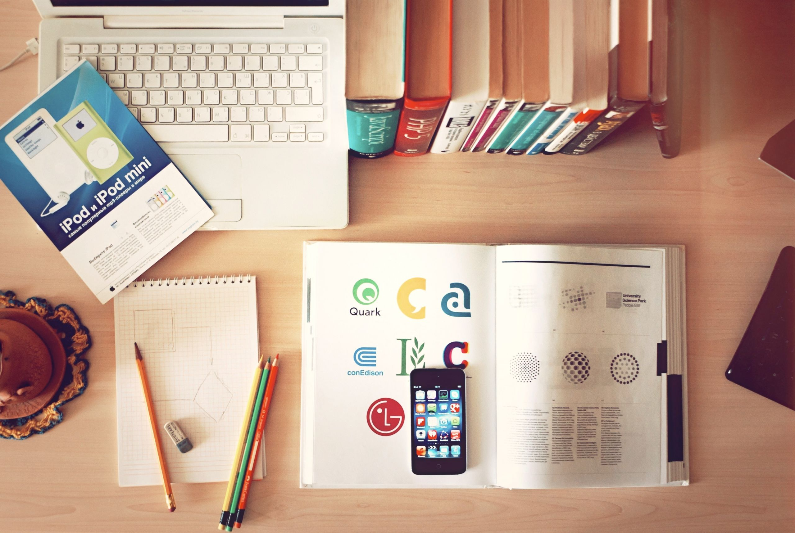 Desk with books, phone, laptop, notebook and stationery
