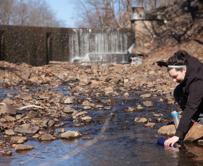 Female filling reusable water bottle from stream