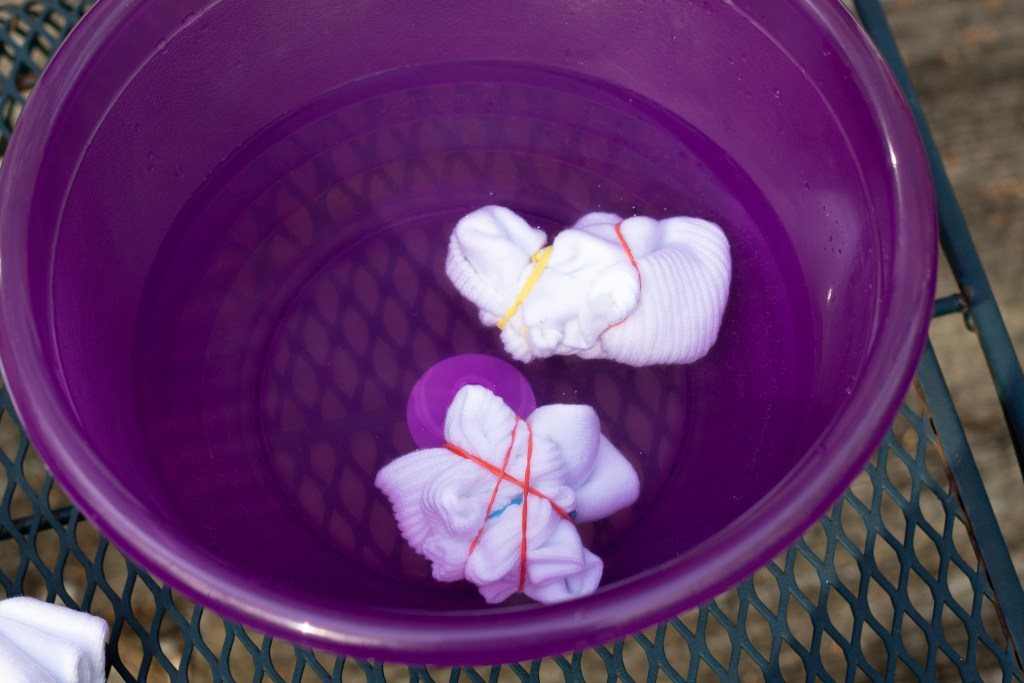 a pair of socks being pre soaked for tie dyeing