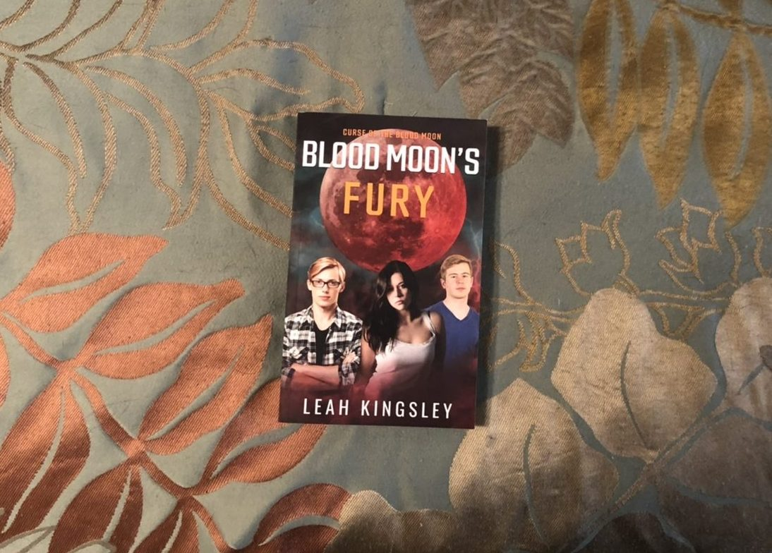 A paperback copy of Blood Moon's Fury rests on a dark green tablecloth printed with copper and gold leaves. The cover of Blood Moon's Fury features three teens standing together beneath a large blood-red moon. The boy on the left has his arms folded across his chest. He has straight strawberry-blonde hair and wears a plaid over-shirt and nerdy-looking glasses. The girl in the middle stares ahead with a determined expression. She has shoulder-length ebony hair and wears a white tank top. The boy on the right has his lips pressed together in a serious frown. He has copper hair and wears a navy-blue t-shirt. The words Curse of the Blood Moon, Blood Moon's Fury are written across the giant red moon. Jagged red lightning can be seen in the background behind the three teens.