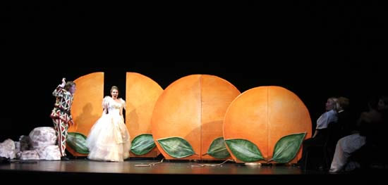 Leandra Ramm picture, wearing white gown and singing with oranges background Take One