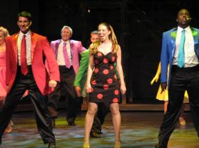 Leandra Ramm picture, singing in group and wearing a red dots dark brown dress on stage Take One