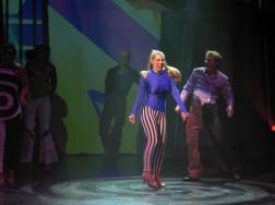Leandra Ramm picture, singing and wearing blueish dress and stripe pants Take Two