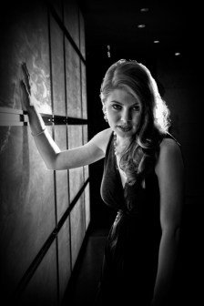 Leandra Ramm black & white picture, wearing black dress leaning on a window Take Two