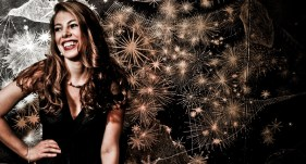 Leandra Ramm picture, wearing black dress leaning on sparkling background Take Three