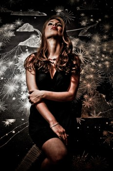 Leandra Ramm picture, wearing black dress leaning on sparkling background Take Two