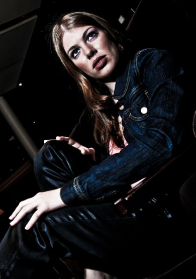 Leandra Ramm picture, wearing orange shirt and dark blue jeans jacket, sitting down