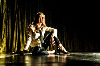 Leandra Ramm picture, wearing white dress and dark pants sitting relax on stage floor