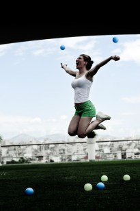 Leandra Ramm picture, wearing white singlet and green short, jumping with balls outdoor