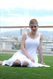 Leandra Ramm picture, wearing white dress sitting pretty outdoor