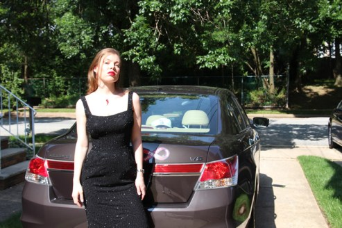 Leandra Ramm picture, wearing black dress leaning on Honda Accord car Take Two