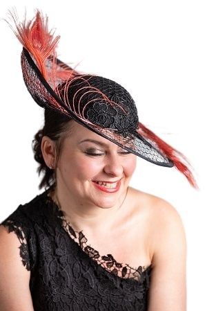 Leanne wearing assymetrical Black hat with Coral Feathers cascading up and down the assymetrical brim. Laughing.