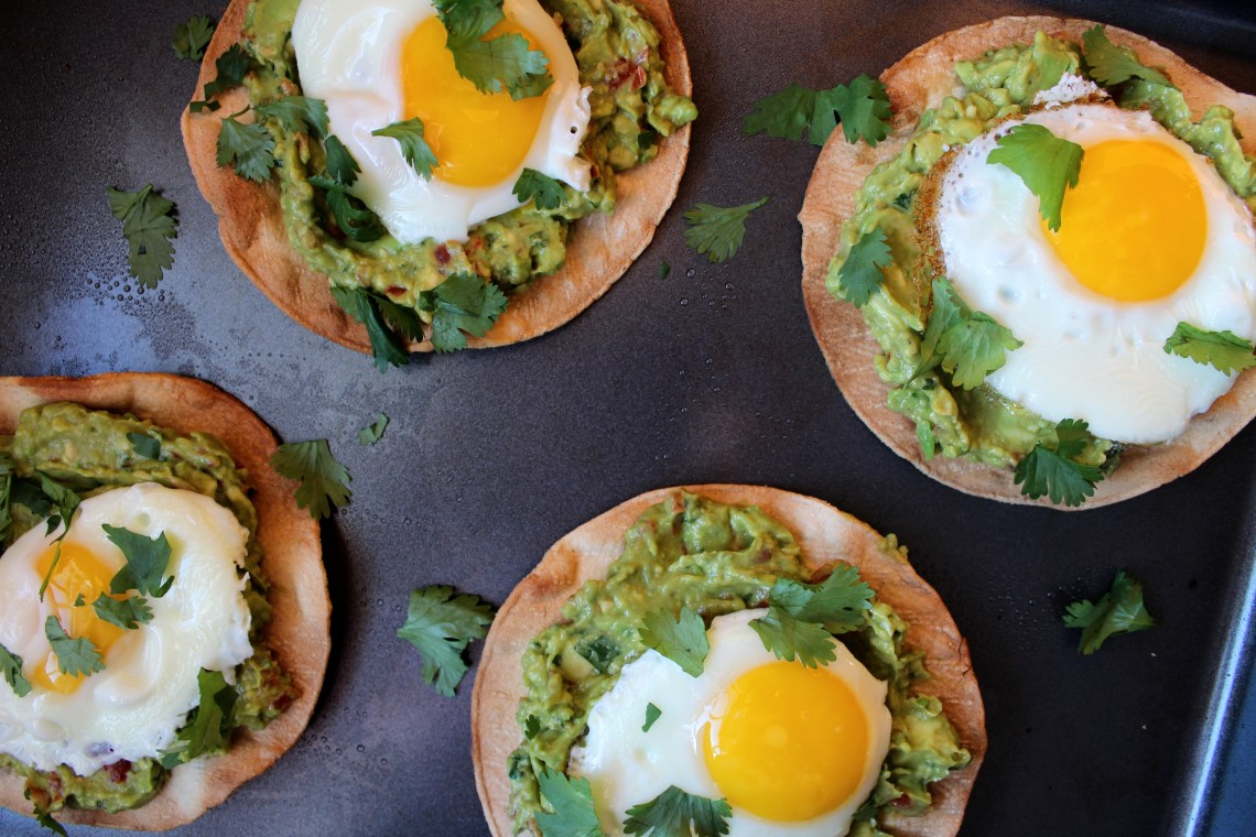 Avocado Breakfast Tostadas - Crispy, oven-baked tortillas topped with fresh guacamole and fried eggs